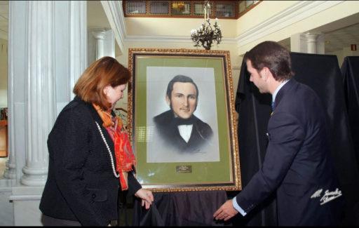 Carmen Calvo mostrando cuadro del artista miguel angel coll